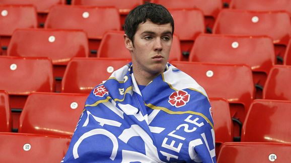 A Chelsea fan sits dejected after his te