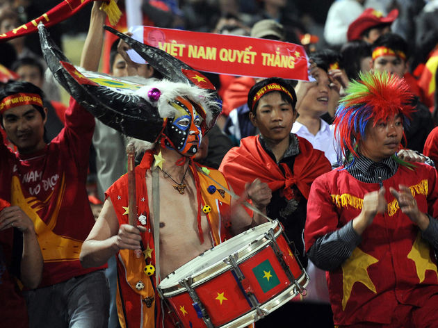 A Vietnamese fan beats a drum during the