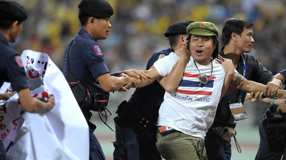 A Thai football fan is escorted by riot