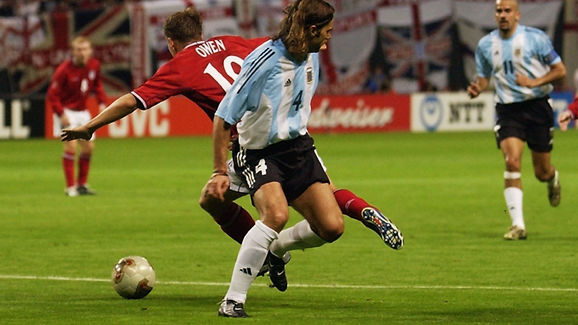 Michael Owen of England is fowled by Mauricio Pochettino of Argentina