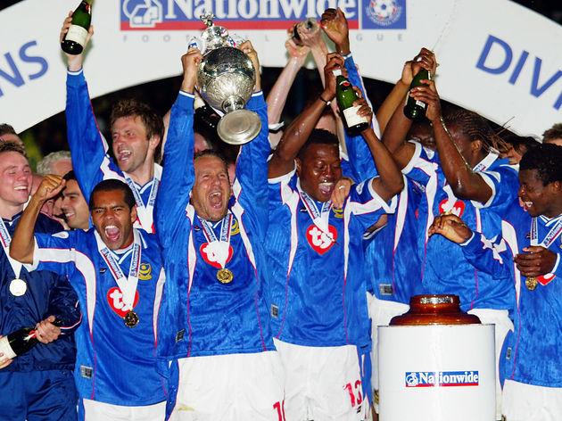 Paul Merson of Portsmouth lifts the trophy up as his team-mates celebrate