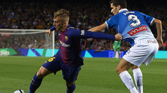 Gerard Deulofeu (L) of Barcelona competes for the ball with Aaron Martin of Espanyol