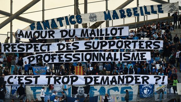 Olympique de Marseille (OM) fans hold a banner reading 'for the love of the OM jersey, the respect of fans and professionalism, is it too much to ask?', prior to the start of the French L1 football match between Olympique de Marseille (OM) and Caen at the Velodrome stadium