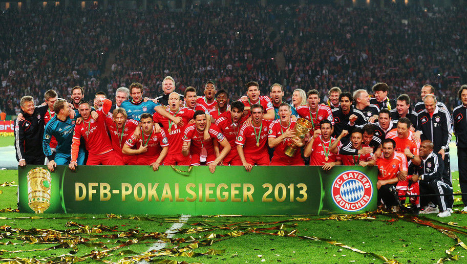 Bayern Munich players celebrate victory with the trophy after the DFB Cup Final match between FC Bayern Muenchen and VfB Stuttgart at Olympiastadion on June 1, 2013 in Berlin, Germany. Bayern become the first German team to win the treble of league, cup and European Cup/Champions League