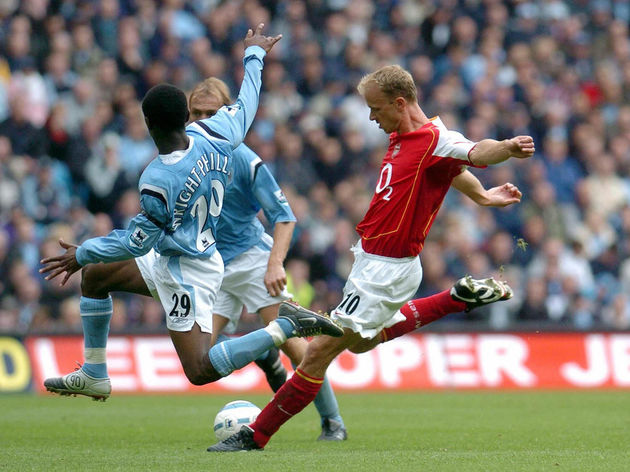 Arsenal's Dennis Bergkamp (r) has his sh