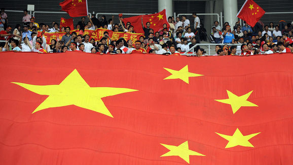 Chinese fans hold up a giant Chinese fla