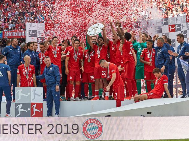 Spieler FC Bayern jubeln mit der Meisterschale
