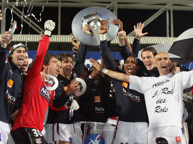 Lyon's players jubilate and hold the tro...