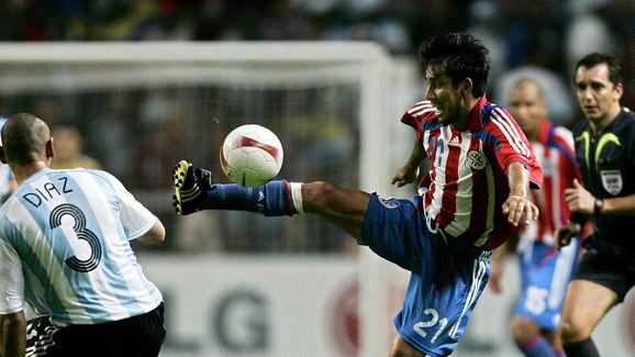 Paraguay?s forward Nelson Cuevas (R) vie...