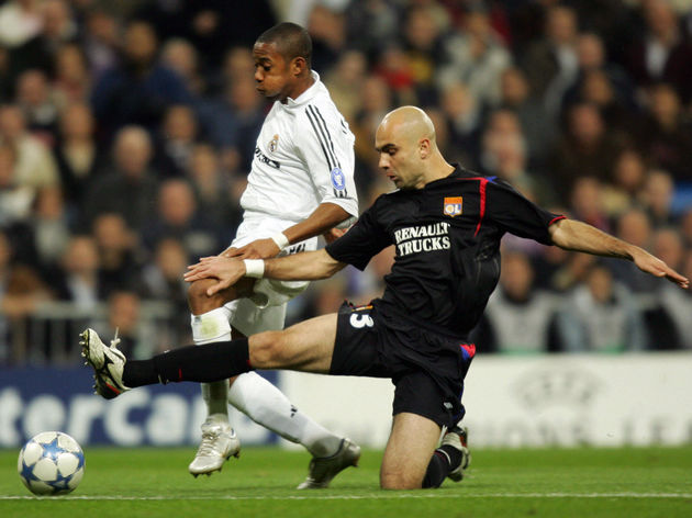 Real Madrid's Robinho (L) is tackled by