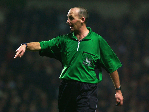 Referee Mike Dean pointing to the ground