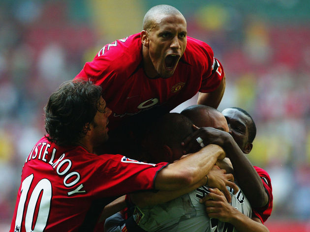 Rio Ferdinand of Manchester United jumps on top of his team-mates as they congratulate goalkeeper Tim Howard