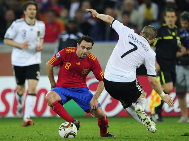 Spain's midfielder Xavi (L) and Germany'