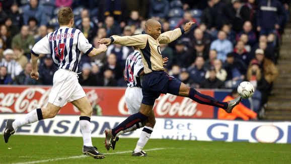 Thierry Henry of Arsenal attempts to control the ball while being challenged by Ronnie Wallwork of West Bromwich Albion