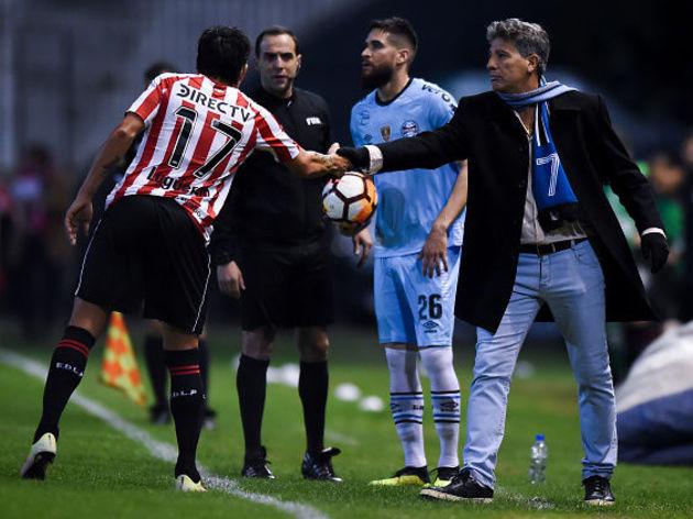 Renato Portaluppi conversa com jogador do Estudiantes enquanto Marcelo Oliveira se prepara para cobrar o lateral
