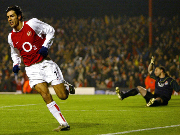Arsenal's Robert Pires (L) runs away fro